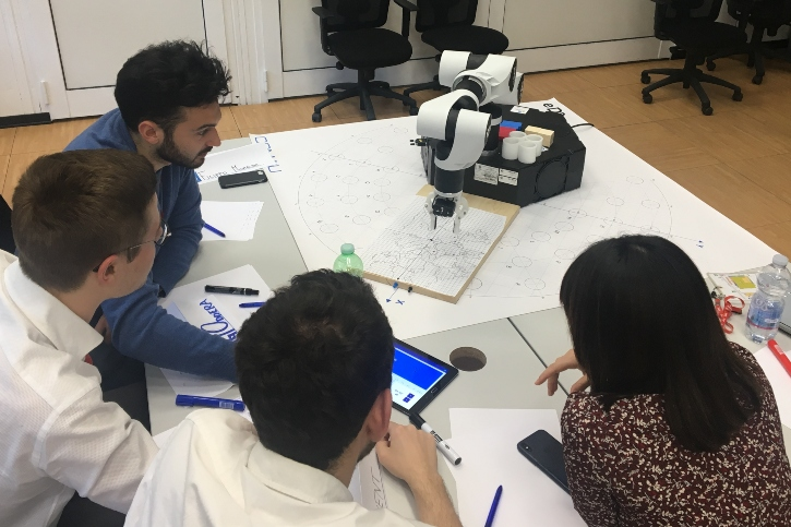 students working in Comau with real robots